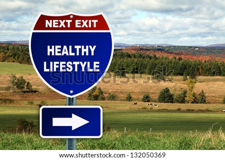 Healthy lifestyle road sign against a beautiful autumn country landscape - stock photo
