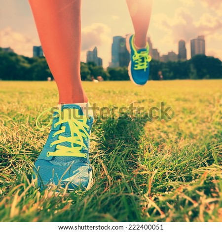 Healthy lifestyle runner - running shoes on woman athlete running shoes on grass. Female jogger womens shoes in Central Park, New York City. - stock photo