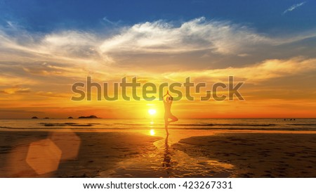 Healthy lifestyle. Silhouette meditation yoga woman on background of the sea and amazing sunset.  - stock photo