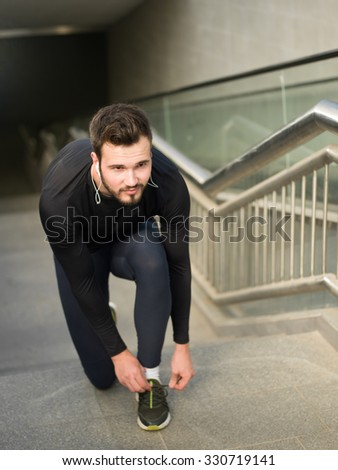 healthy lifestyle sports man tying shoelace before running, gold