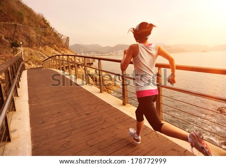 healthy lifestyle sports woman running on wooden boardwalk seaside - stock photo