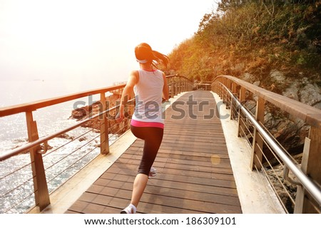 healthy lifestyle sports woman running on wooden trail seaside - stock photo