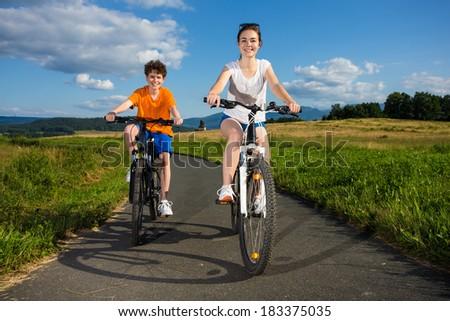 Healthy lifestyle - teenage girl and boy riding bikes - stock photo