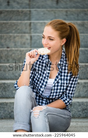 Healthy lifestyle  - teenager eating puffed bread outdoor sitting on stairs - stock photo
