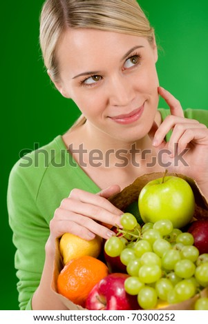 Healthy lifestyle - thoughtful woman with fruit shopping paper bag on green background