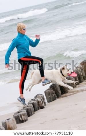 Healthy lifestyle - woman running with dog on the beach
