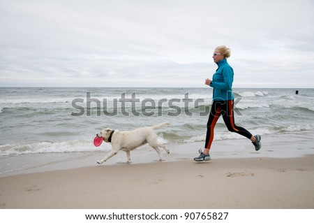Healthy lifestyle - woman running with dog on the beach - stock photo