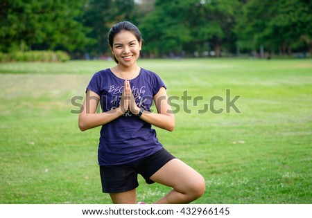 healthy lifestyle - Young adult asian happy woman do yoga in green grass field, standing one leg, chubby girl lost weight with smile, lose weight