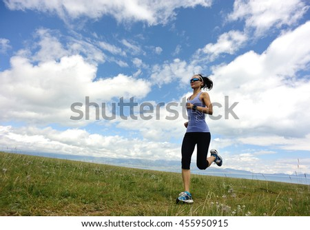 healthy lifestyle young fitness woman runner running on beautiful trail in grassland