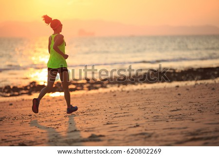 Healthy lifestyle young fitness woman running at morning beach