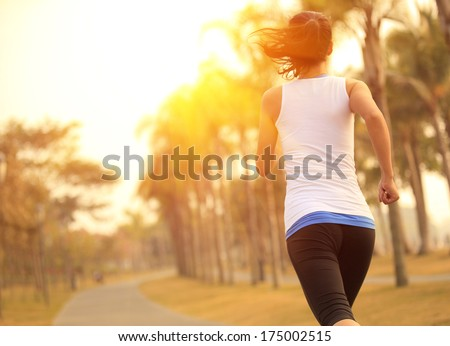 healthy lifestyle young sporty asian woman running at tropical park - stock photo