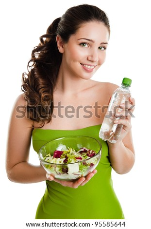 Healthy lifestyle - young woman eating salad and holding the bottle of water smiling happy looking at camera. - stock photo