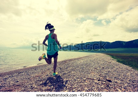 healthy lifestyle young woman runner running on sunrise seaside trail