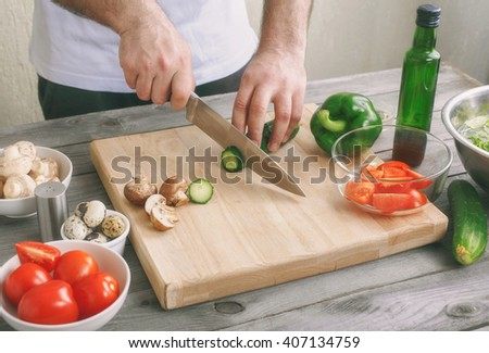 Healthy lifestyles concept. Man prepares a salad of fresh vegetables on a wooden table in rustic kitchen - stock photo