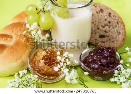 Healthy light breakfast with bun, bread, honeycomb, jam, glass of fermented milk , grapes and white tiny flowers on light green spring background - stock photo
