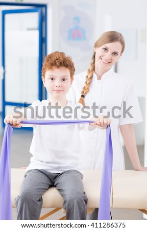 Healthy little red head boy exercising with elastic band during physiotherapy in clinic. Behind him young smiling physiotherapist