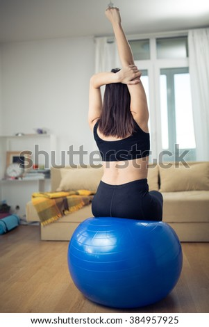 Healthy living fit woman using fitness pilates ball for exercise workout.After work relaxation and stretch every day routine in small improvised home space.Short exercises to do at home.Stretching out - stock photo