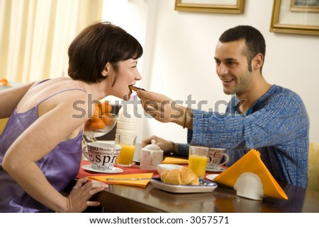healthy living: young couple having breakfast at home - stock photo