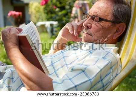 Healthy looking old man is his late 70s sitting in garden at home and reading book, outdoor. - stock photo