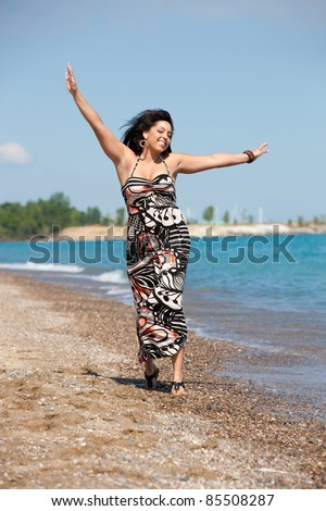 Healthy Looking Plus Size Model Walking on Beach - stock photo