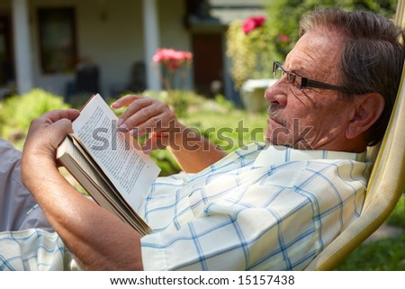 Healthy looking senior man is his late 70s sitting in garden at home and reading book, outdoor. - stock photo