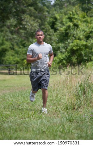 Healthy Looking Young African American Man Jogging in the Woods - stock photo