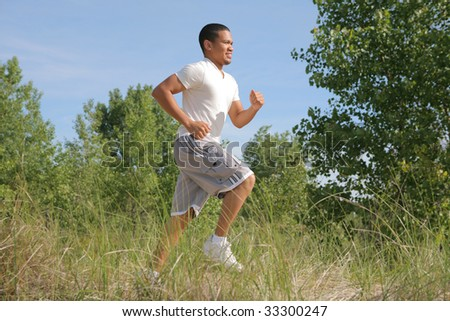 Healthy Looking Young Man Jogging in the Woods - stock photo