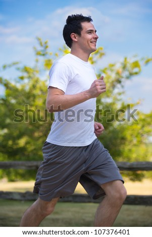 Healthy Looking Young Man Jogging in the Woods Under Morning Sunlight