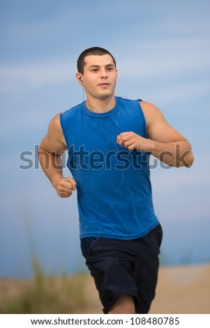 Healthy Looking Young Man Jogging under Morning Blue Sky by Beach - stock photo
