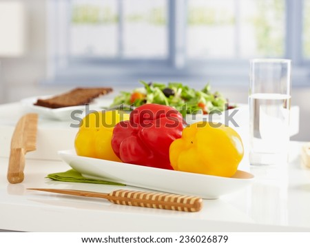 Healthy, low calorie food on tabletop, plate of sweet peppers, salad and brown bread. - stock photo