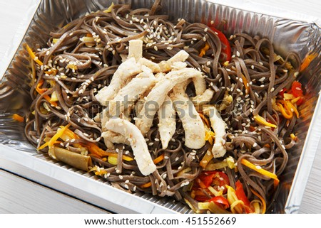 Healthy lunch and diet concept. Take away of fitness food. Weight loss nutrition in foil boxes. Brown rice vermicelli noodles with turkey meat at white wood, closeup - stock photo