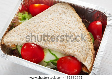 Healthy lunch and diet concept. Take away of fitness food. Weight loss nutrition in foil boxes. Sandwiches with whole-grain bread, cucumber and tomatoes at white wood, closeup - stock photo
