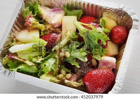 Healthy lunch and diet concept. Take away of fitness food. Weight loss nutrition in foil boxes. Pine nuts, pea and strawberry salad with lettuce at white wood, closeup - stock photo