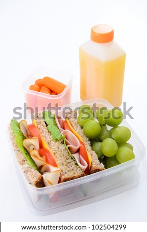 Healthy lunch box with turkey and ham sandwich with grapes, carrots and orange juice - stock photo