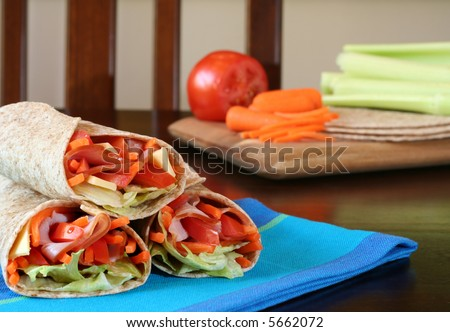 Healthy lunch, ham, cheese and vegetables wrapped in whole wheat tacos. - stock photo