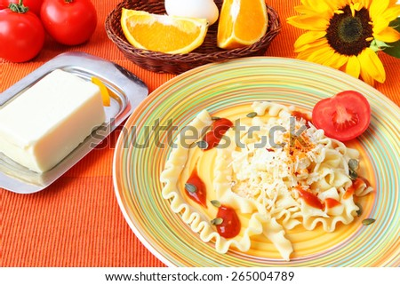 Healthy lunch served on a bright color napkin with sunflower - Pasta with tomato sauce,grated parmesan cheese,grains of pumpkin and herbs with addition of fresh tomatoes,butter,eggs and sliced orange - stock photo