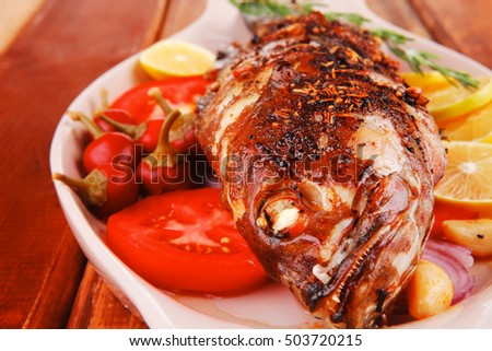 healthy lunch : whole fried sea sunfish on wooden table with lemons peppers and tomatoes and rosemary twig