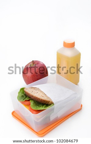 Healthy lunchbox with sandwich, red apple and orange juice - stock photo