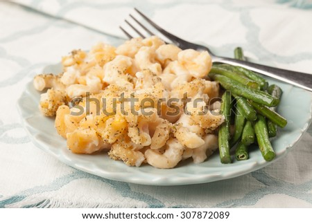 Healthy macaroni and cheese with pureed cauliflower and stir-fried Asian green beans - stock photo