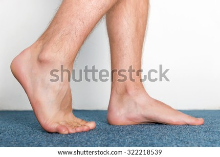 Healthy male feet making a step over home-like background. - stock photo