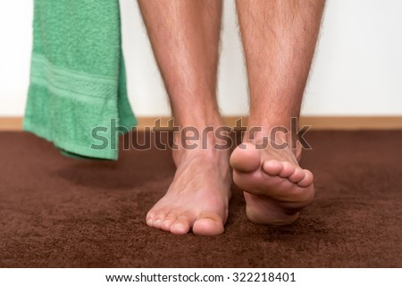 Healthy male feet with towel stepping towards the bathroom. - stock photo