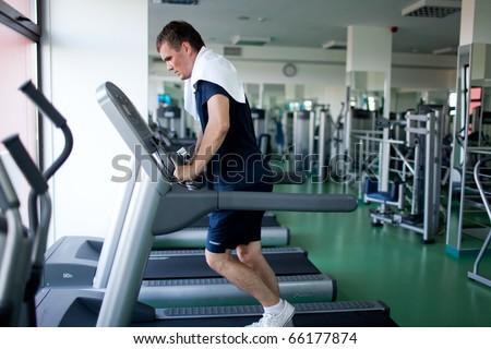 Healthy man a treadmill in a sport center - stock photo