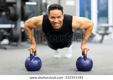 healthy man doing pushup exercise with kettle bell in gym - stock photo