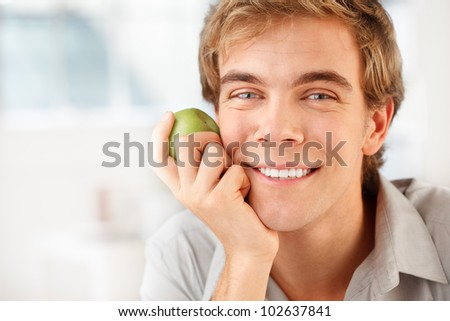 healthy man holding green apple indoors at home - stock photo