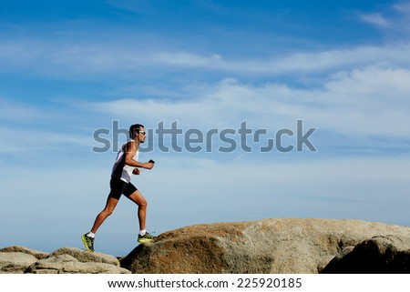 Healthy man in sportswear running fast over the rocks on sky background, healthy lifestyle and sport concept - stock photo