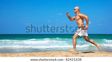 Healthy man running on the beach, doing sport outdoor, freedom, vacation, heath care concept with copy space over natural background - stock photo