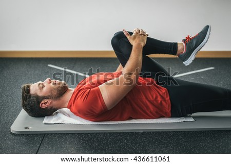 healthy man stretching leg before gym workout. Fitness strong male athlete. Male young fit exercising. - stock photo