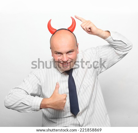 Healthy man with devil horns showing thumbs up. - stock photo