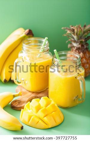 healthy mango pineapple smoothie in mason jars - stock photo