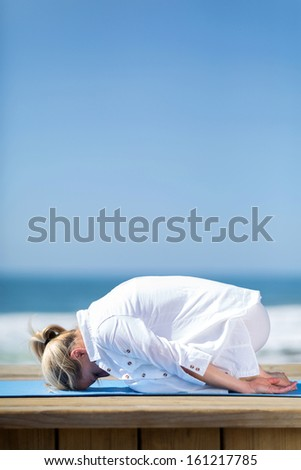 healthy mature yoga exercise on beach